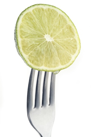 slice of lime pierced on a fork against plain background Stock Photo - 12681395