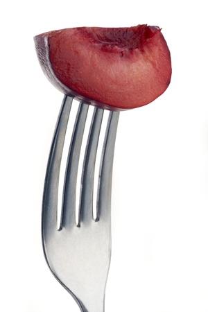 slice of plum pierced on a fork against plain background Stock Photo - 12681383