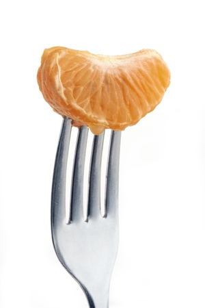 slice of orange pierced on a fork against plain background Stock Photo - 12681396
