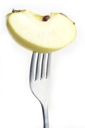slice of apple pierced on a fork against plain background Stock Photo - 12681397