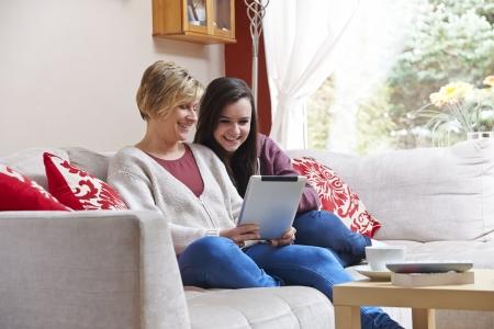 net surfing: Madre e figlia godono la navigazione in rete con tablet, mentre relax a casa con il caff� Archivio Fotografico