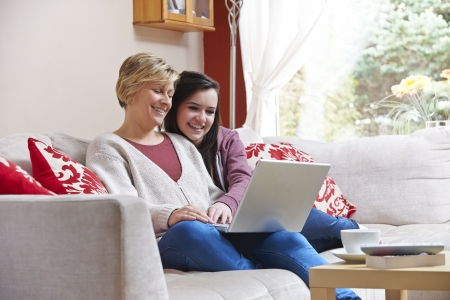 Mother and daughter smiling at laptop while using web cam Stock Photo