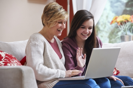 Mother and daughter smiling at laptop while using webcam photo
