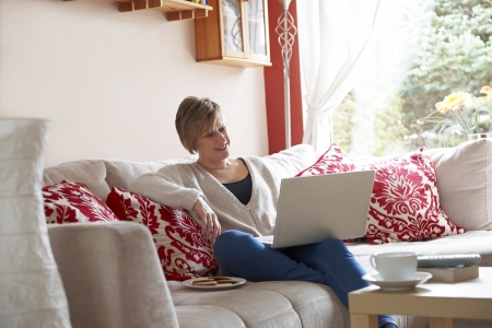 Mother enjoying surfing on the net while relaxing at home with coffee photo
