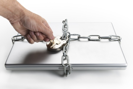 hand key: Mans hand placing key in padlock which is chained to closed laptop computer Stock Photo