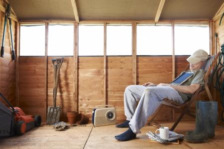 Man zit in deckchair in slaap vallen in de schuur