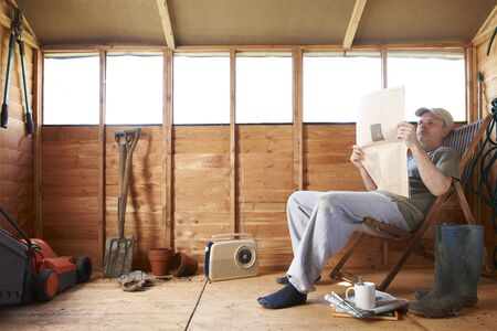 Man checking share prices while sitting in deckchair in his garden shed photo