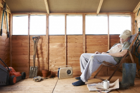 sheds: Man sitting in deckchair falling asleep in the shed Stock Photo