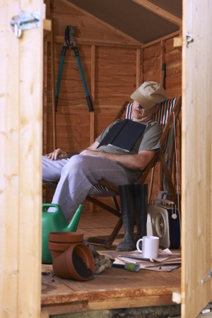 siesta: Man sitting in deckchair falling asleep in the shed while reading book