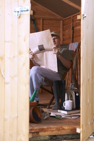 share prices: Man checking share prices while sitting in deckchair in his garden shed Stock Photo