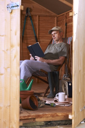 sheds: Man reading book while sitting in deckchair in his garden shed Stock Photo