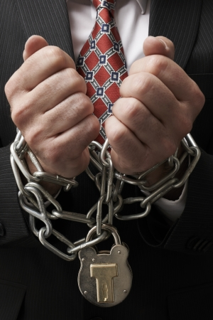 in bondage: Close up of businessmans hands tied in heavy chains with padlock
