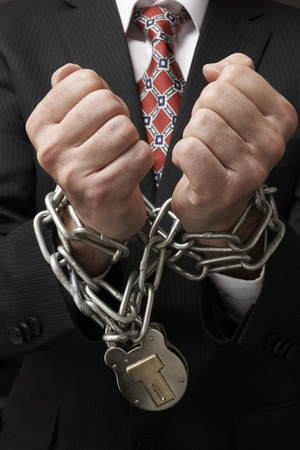 confine: Close up of businessmans hands tied in heavy chains with padlock