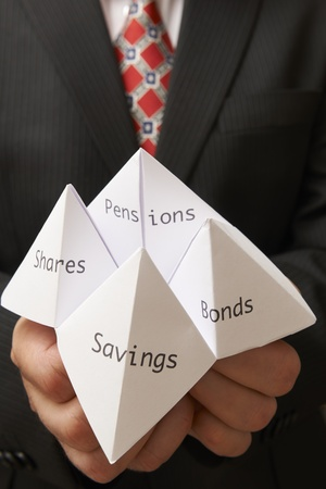Business man holding paper origami fortune teller with savings,bonds,shares and pensions written on it Stock Photo