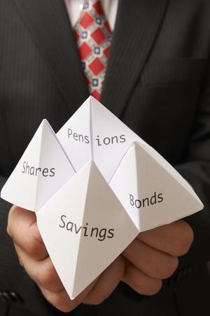 adivino: Hombre de negocios la celebración de papel origami adivino con ahorros, bonos, acciones y pensiones escritos en ella