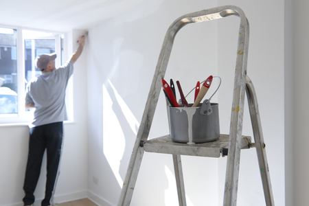 painter and decorator: man decorating a room with ladder and paint pot in foreground