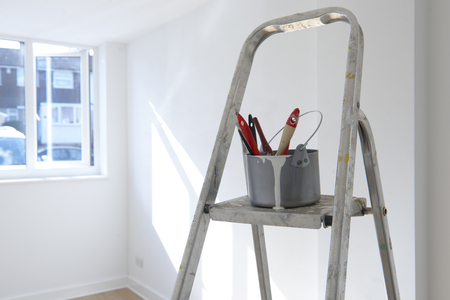 paint tin: ladder with paint pot and brushes standing in empty room Stock Photo