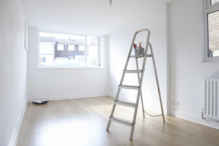 ladder with paint pot and brushes standing in empty room Stock Photo