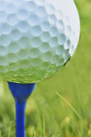 Close-up of golf ball resting on blue tee with grass and space for copy