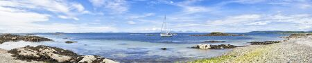 Panoramic view of sailing boat moored at Ronachan Point, Kintyre off the West coast of Scotland