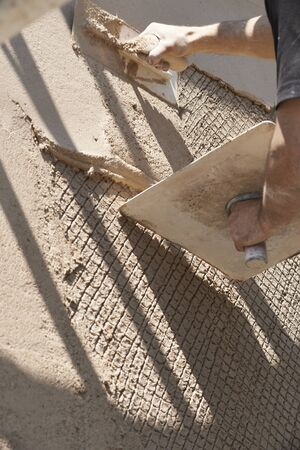 Man using trowel to plaster outside wall of house Standard-Bild