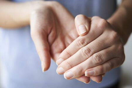 Close Up of a Woman rubbing her hands together with disinfectant Imagens