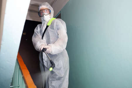 Man performs sanitization at the entrance of a house from coronavirus, infections insects or mice In protective overalls Stockfoto