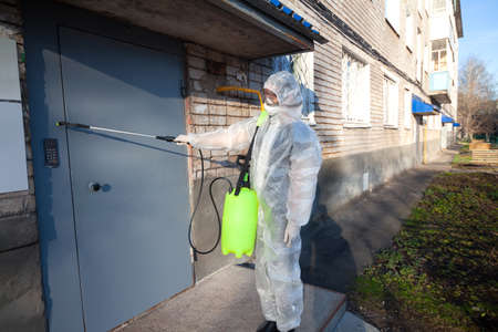 Man performs sanitization at the entrance of a house from coronavirus, infections insects or mice In protective overalls