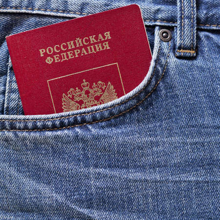 Red Russian passport in pocket of blue jeans photo