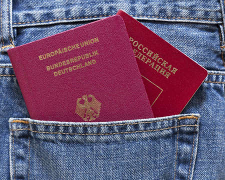 German and Russian passports in back pocket of a blue jeans Stock Photo