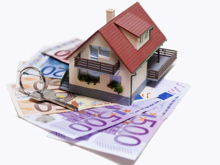 economise: House with Euro banknotes and house key over white background Stock Photo