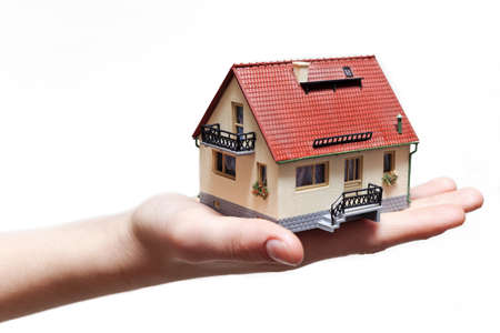 renter: Hand holding small miniature house isolated on white background
