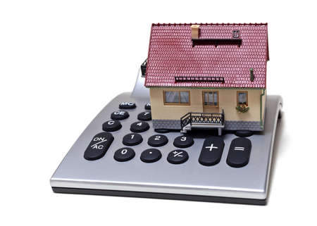 mortgaging: Model house and calculator isolated on white background