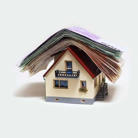 mortgaging: House with Euro banknotes on white background Stock Photo