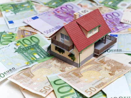 mortgaging: House over Euro banknotes background