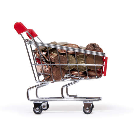 monetary policy: a shopping cart is filled with well-euro coins on white background