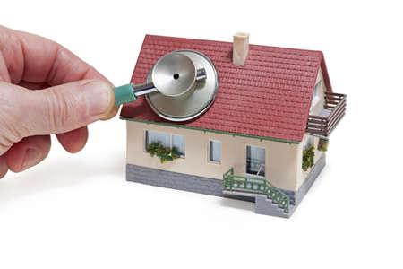 Huis diagnostiek Model huis met hand en stethoscoop op een witte achtergrond
