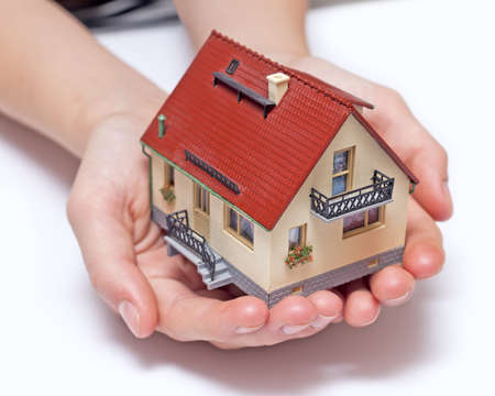 Hands holding small miniature house  photo
