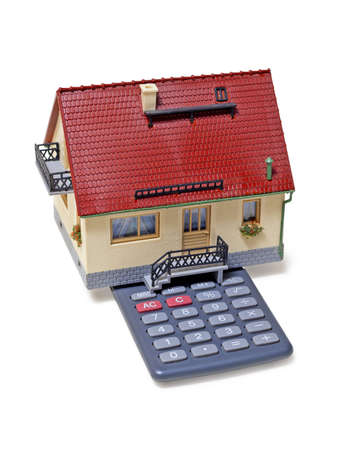 mortgaging: Model house and calculator on white background