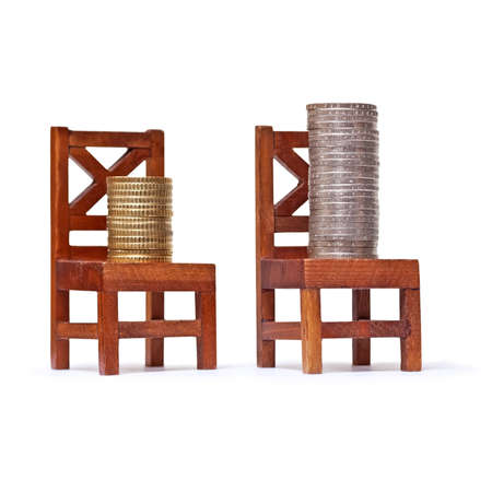 minimum wage: Stack of euro coins on wooden chairs on white