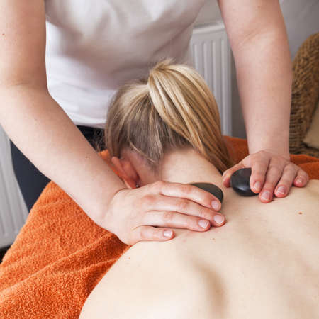 stone bowl: Woman relaxing while having a hot stone massage