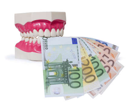 Plastic dentures with Euro banknotes over white background  High treatment costs Stock Photo - 19595903