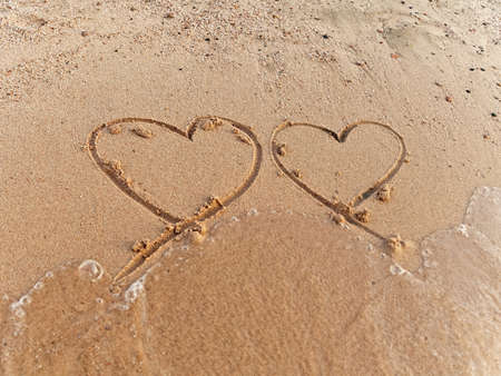 two hearts on the sand beach photo