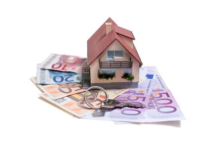 mortgaging: House with Euro banknotes and house key over white background Stock Photo