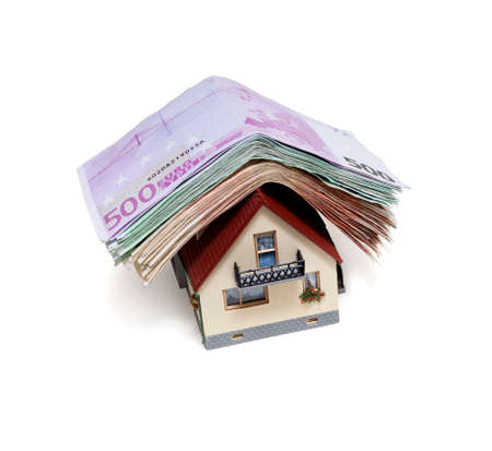 mortgaging: House with Euro banknotes  over white background Stock Photo