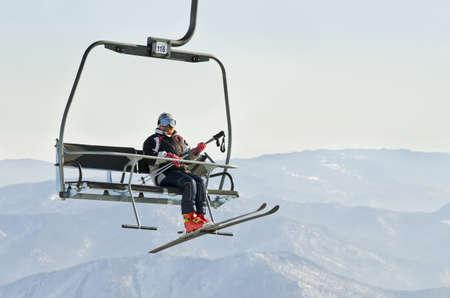Skier on ski lift at resort in Siberia photo
