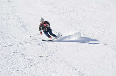 Female skier on the mountain side on a sunny day photo