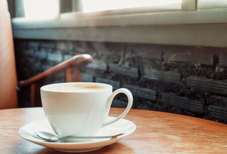 A cup of coffee on the wooden table near window with vintage color. Stock Photo