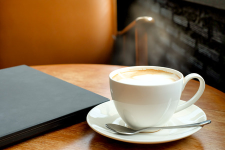 A cup of coffee on the wooden table with black laptop and brown chair. (vintage color) Stock Photo