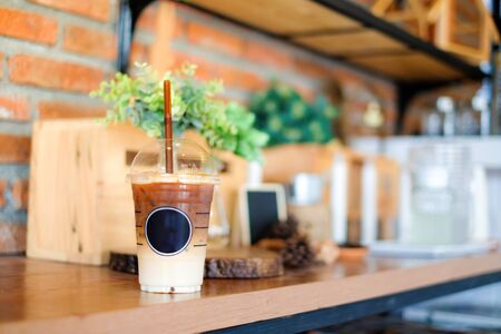 Iced coffee with straw in plastic cup on brown wooden table with some decoration background (selective focus and sunlight)